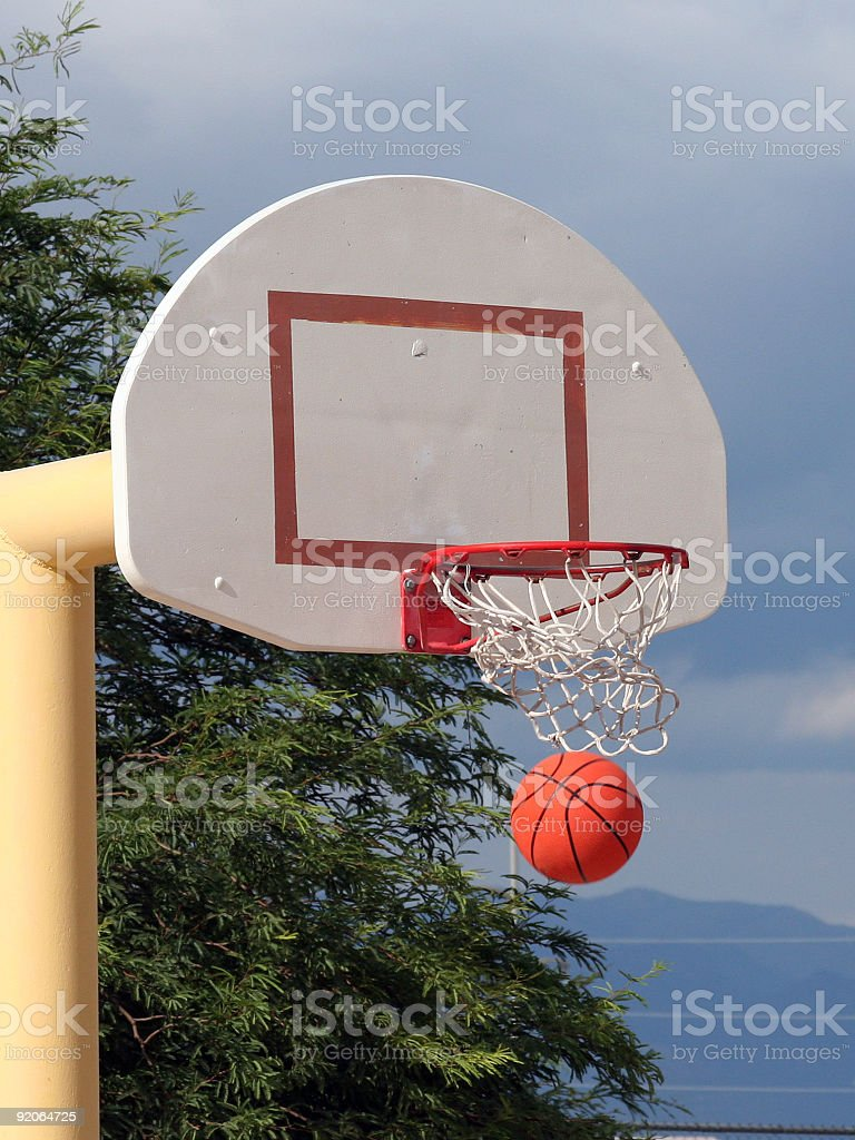 A basketball swishes through the net.