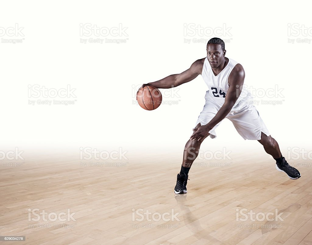 Basketball Player dribbling on a hardwood court stock photo