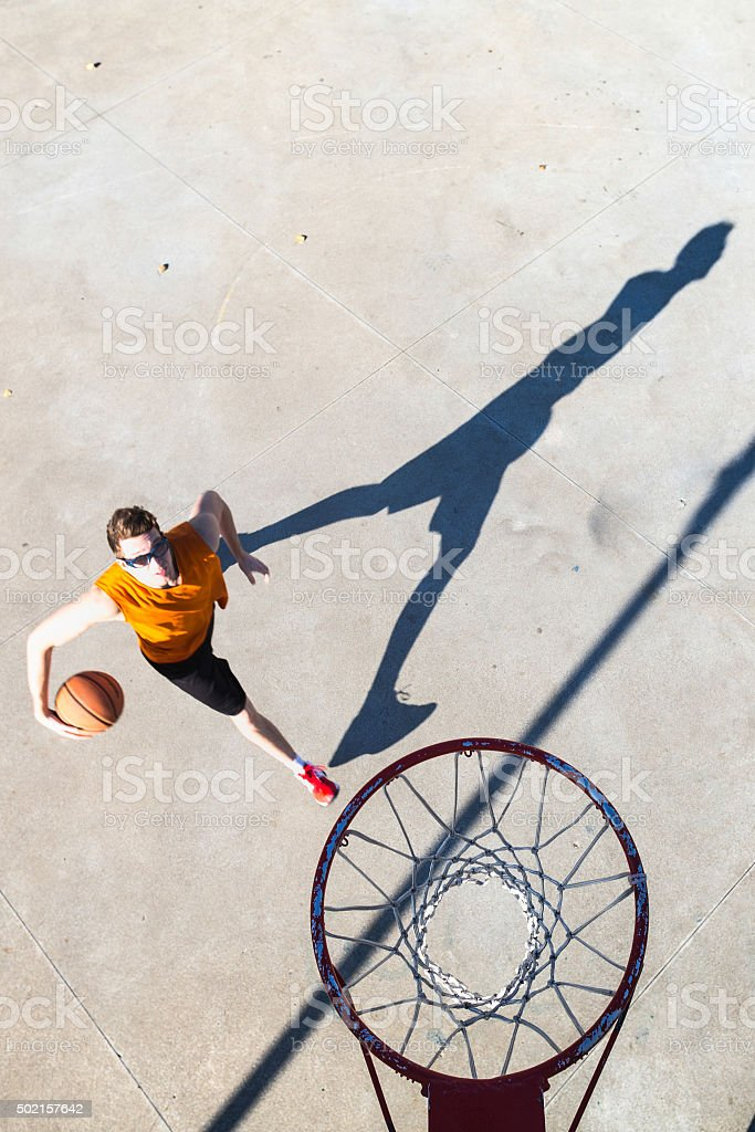 Basketball player goes toward the hoop stock photo