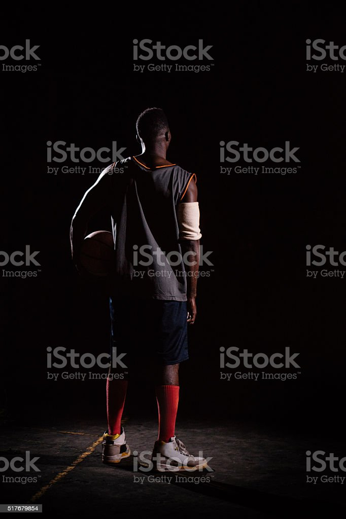Basketball Player Holding Basketball on Hip in Night stock photo