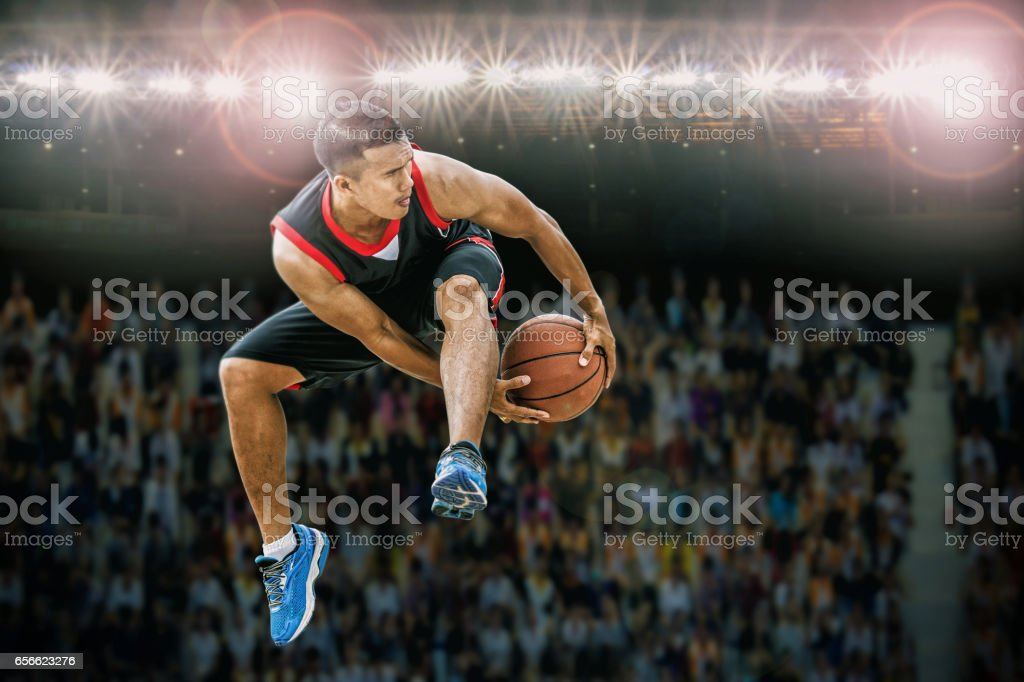 basketball player jumping and dribbling ball in the air,Action in the stadium during match stock photo