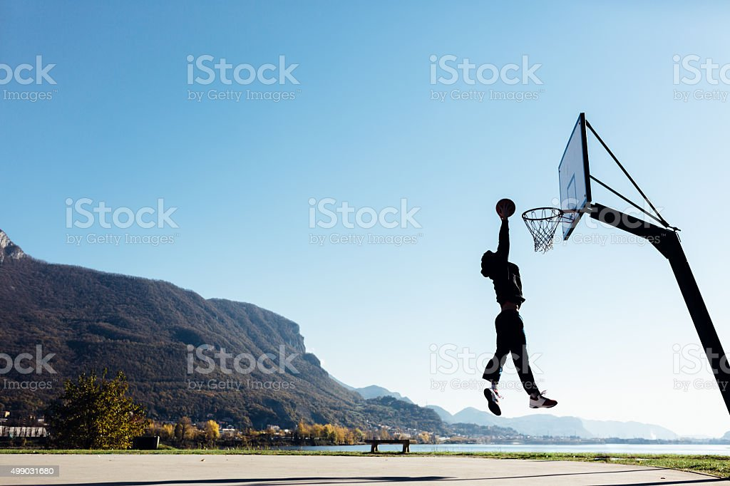 Basketball player jumping and placing ball in the hoop stock photo