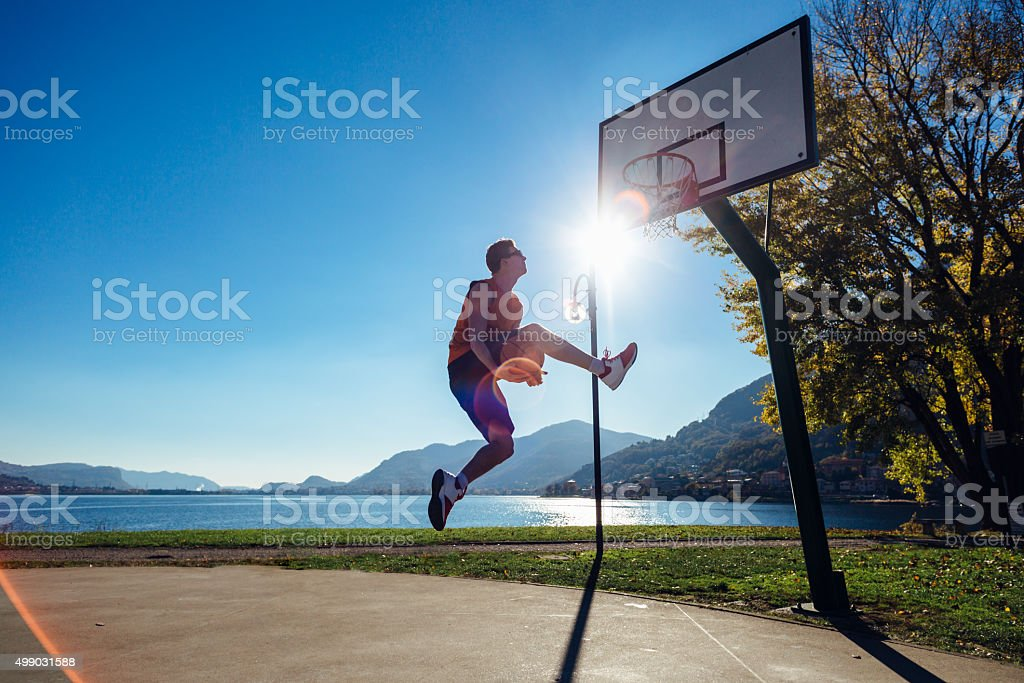 Basketball player jumping to the hoop stock photo