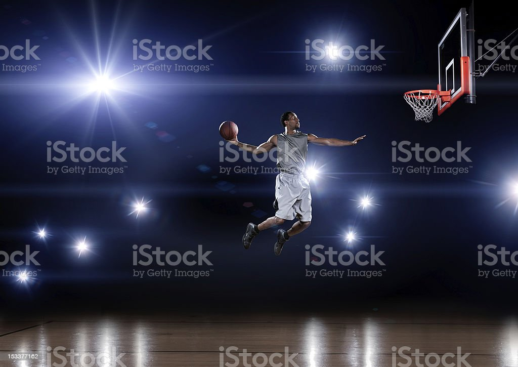 Basketball player jumping toward the net stock photo