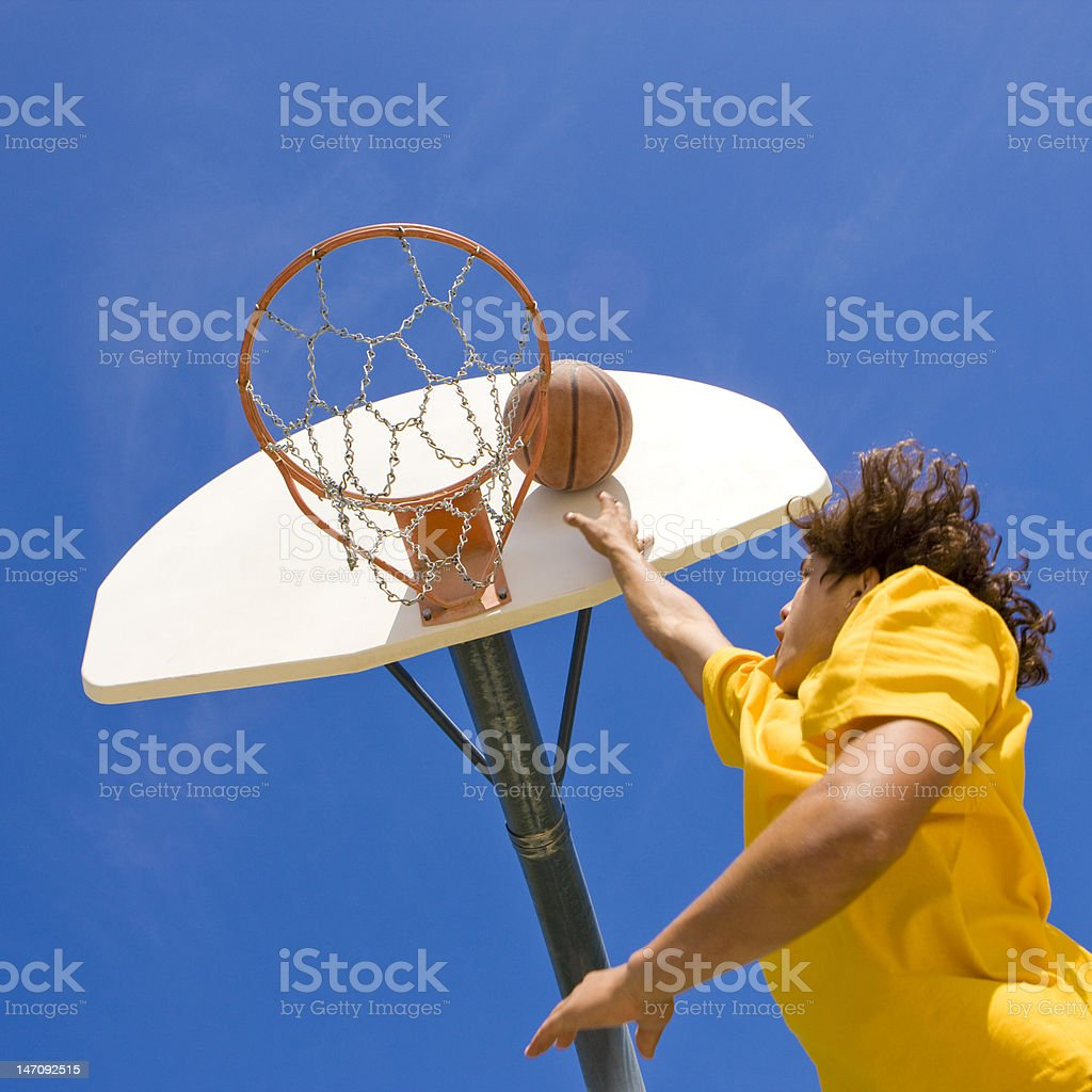 Basketball player jumps and shoots stock photo