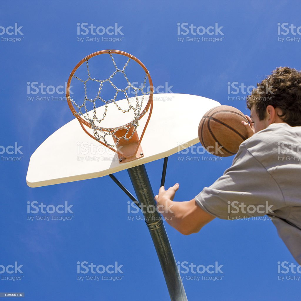 Basketball player jumps for hoop stock photo
