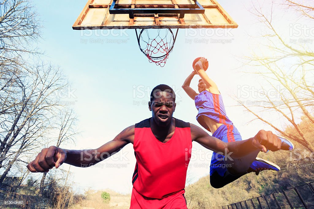 Basketball player makes slam dunk jump as background stock photo
