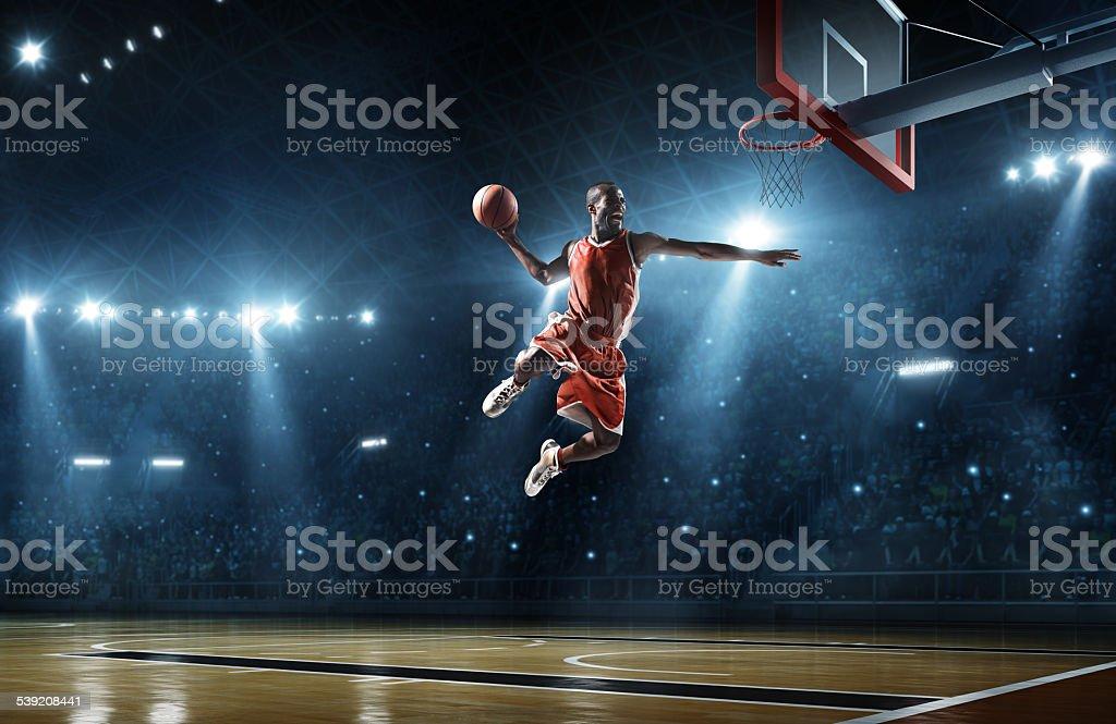 Basketball player makes slam dunk stock photo