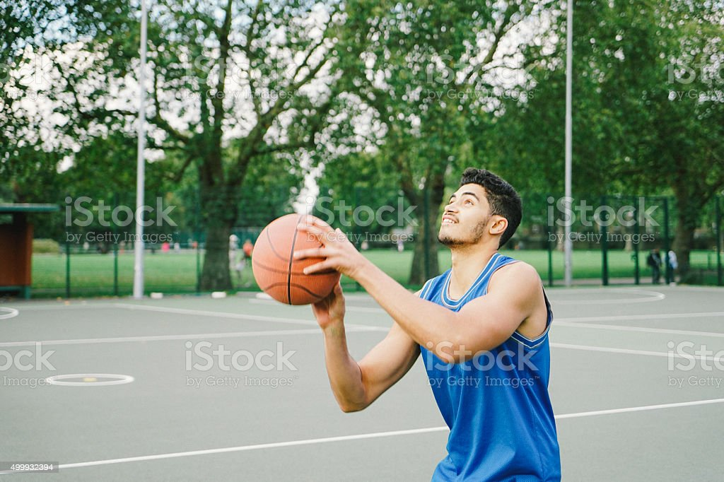 Basketball Player On The Court, Preparing To Dunk Ball stock photo