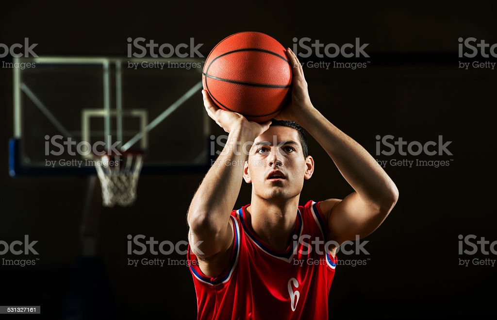 Front view of basketball player shooting at the hoop.