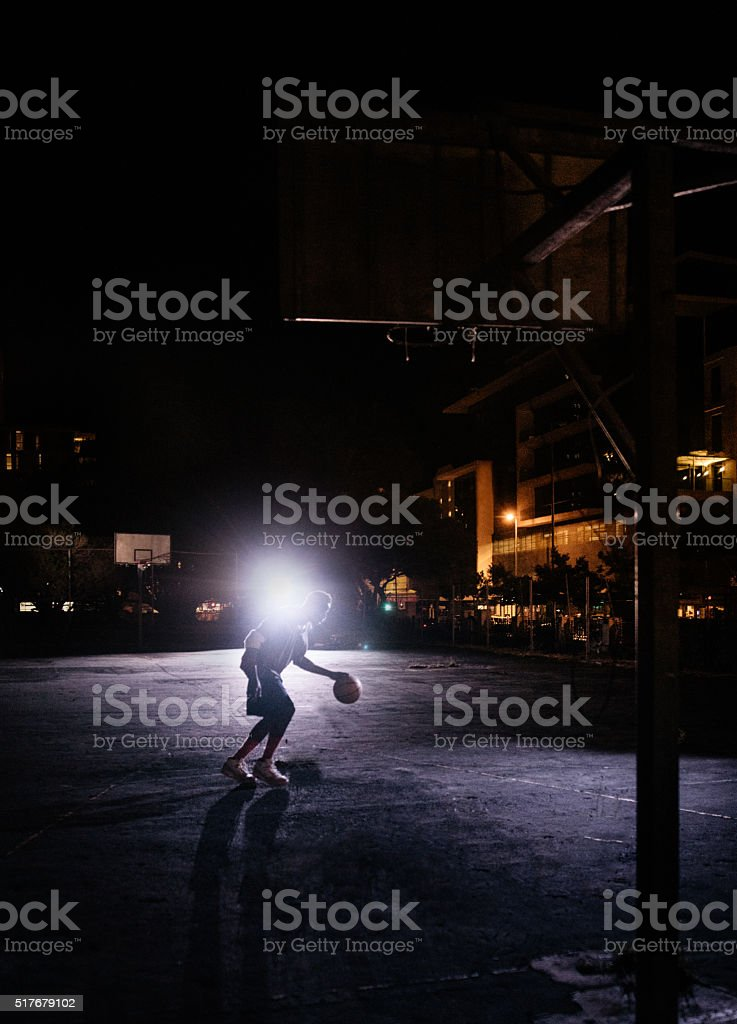 Basketball Player Practicing Alone on Court at Night stock photo