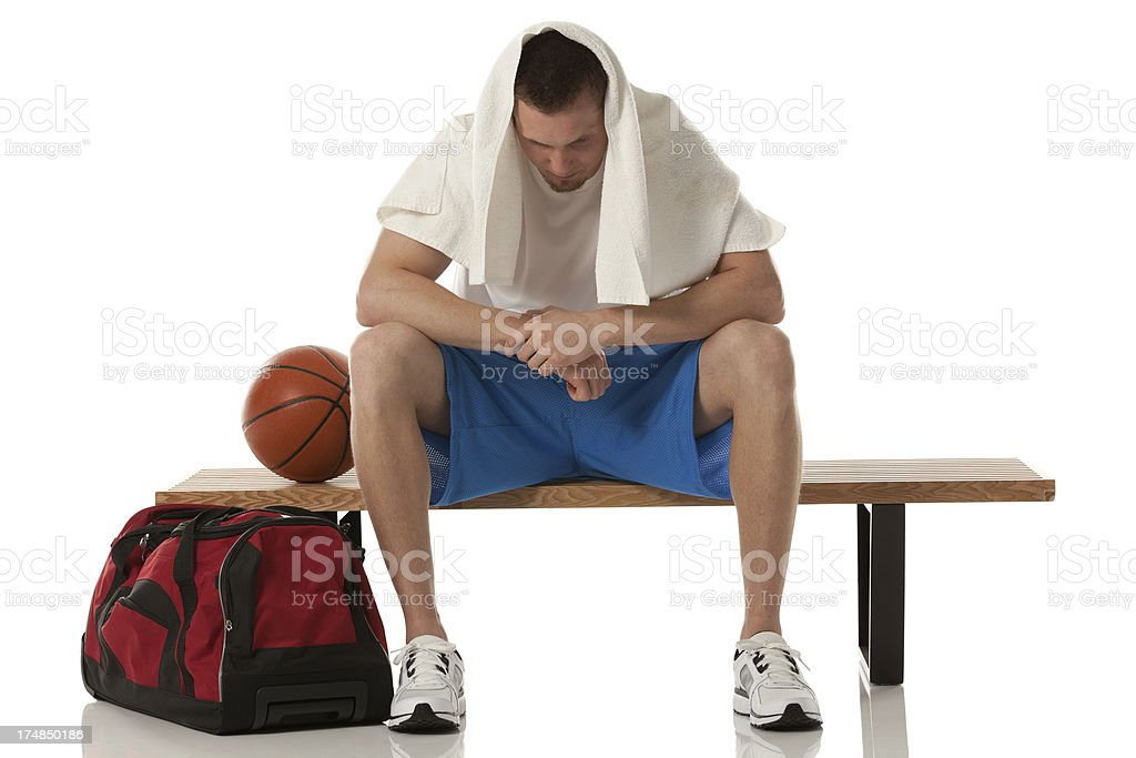 Basketball player resting on a bench royalty-free stock photo