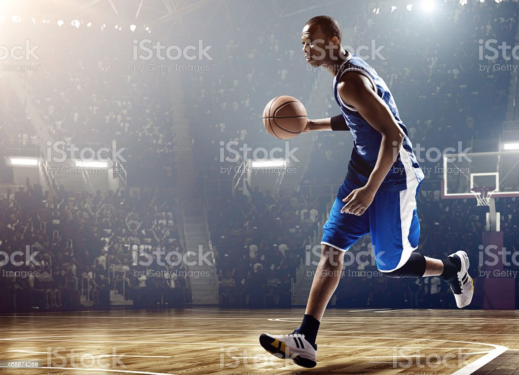 Basketball player running with ball in stadium stock photo