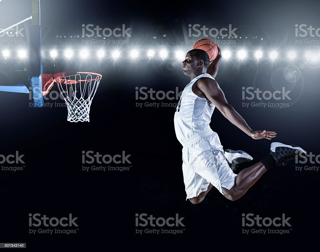 Basketball Player scoring an athletic, amazing slam dunk stock photo