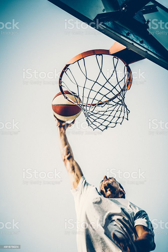 Basketball player slam dunking ball stock photo