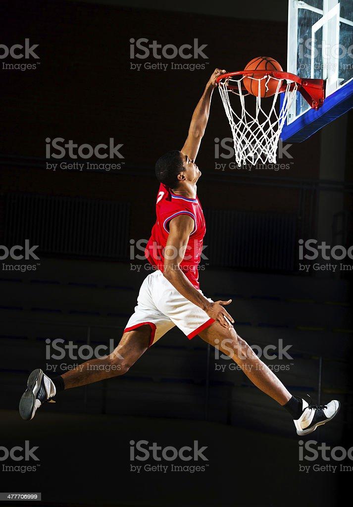 Basketball player slam dunking the ball. stock photo