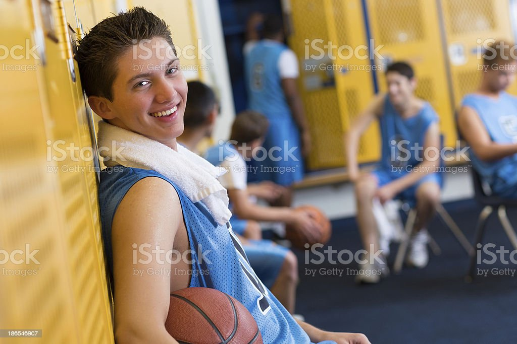 Basketball player smiles in locker room after game stock photo