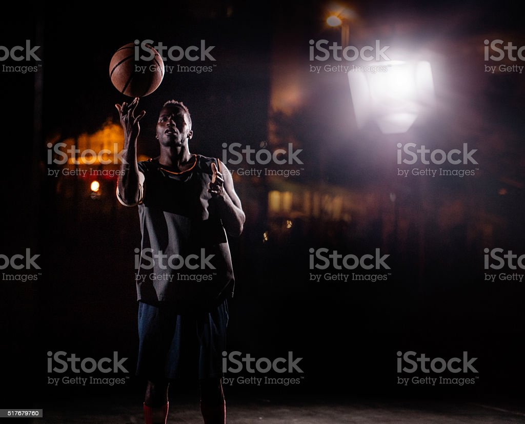 Basketball Player Spinning Ball on Finger on Court in Night stock photo