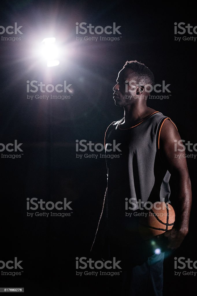 Basketball Player Standing Facing Left and Holding Ball in Night stock photo