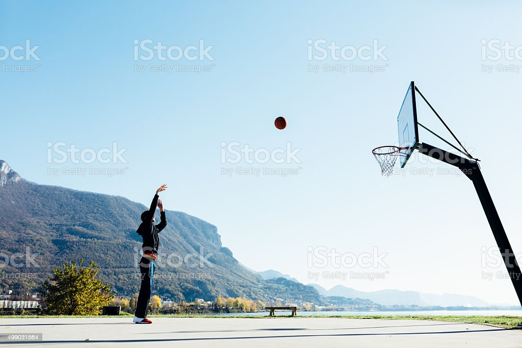 Basketball player throwing ball toward hoop stock photo