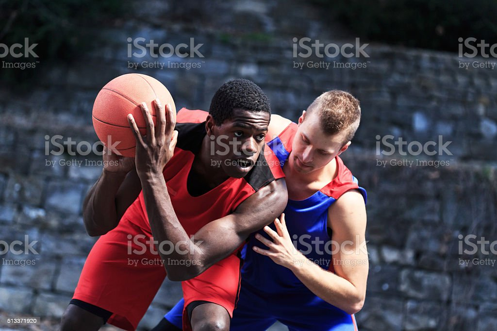 Basketball Player try to shoots against defender - black background stock photo