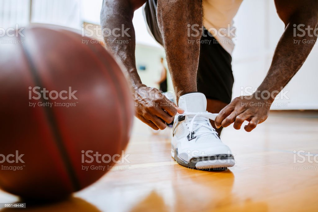 Basketball player tying up his shoelaces stock photo