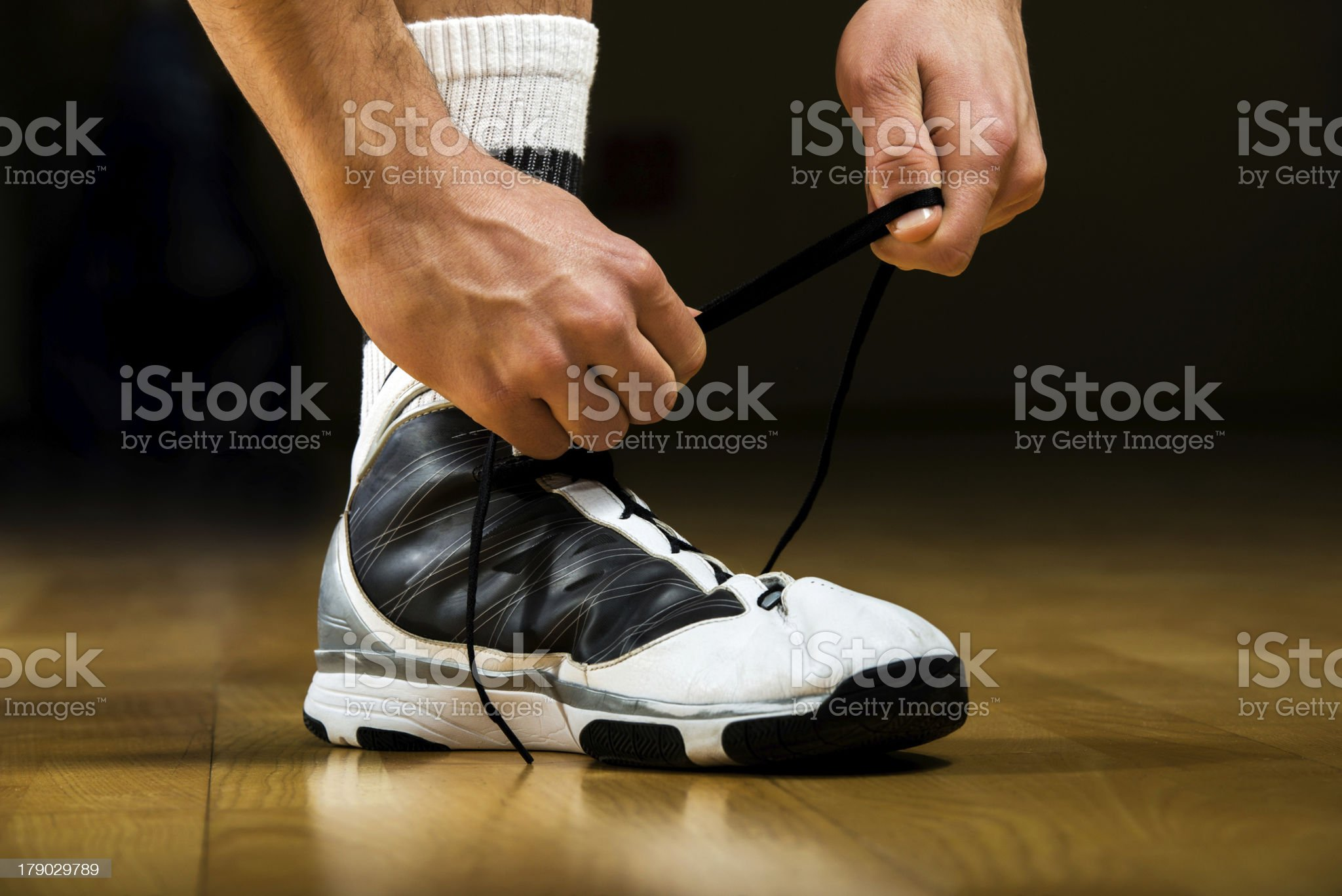 Basketball player tying up shoelaces. royalty-free stock photo