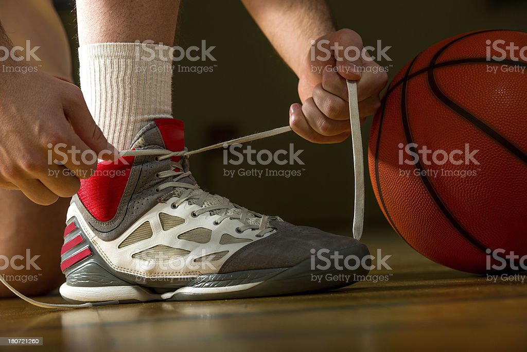 Basketball player tying up the shoelace. royalty-free stock photo