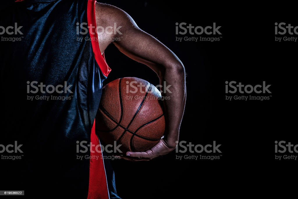 basketball player with a ball on dark background stock photo