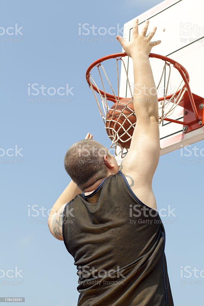Basketball player throw the ball through the basket