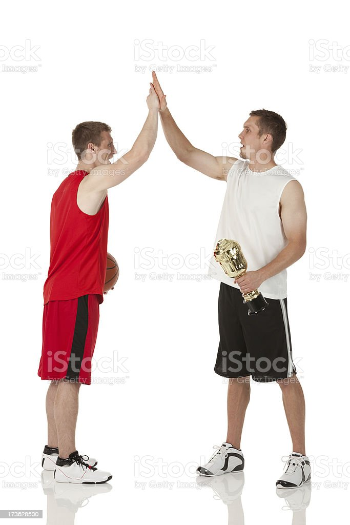 Basketball players giving high-five to each other royalty-free stock photo