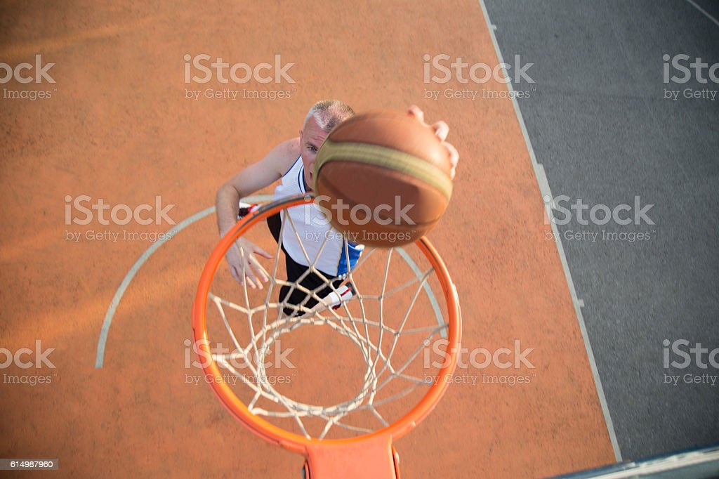 Basketball street player making a slam dunk stock photo
