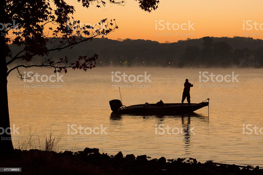 Bass Fisherman on Lake at Dawn stock photo