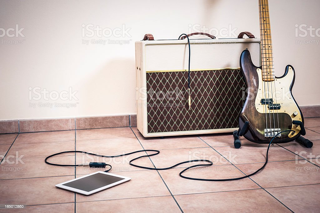 Bass Guitar, Amp And Digital Tablet stock photo