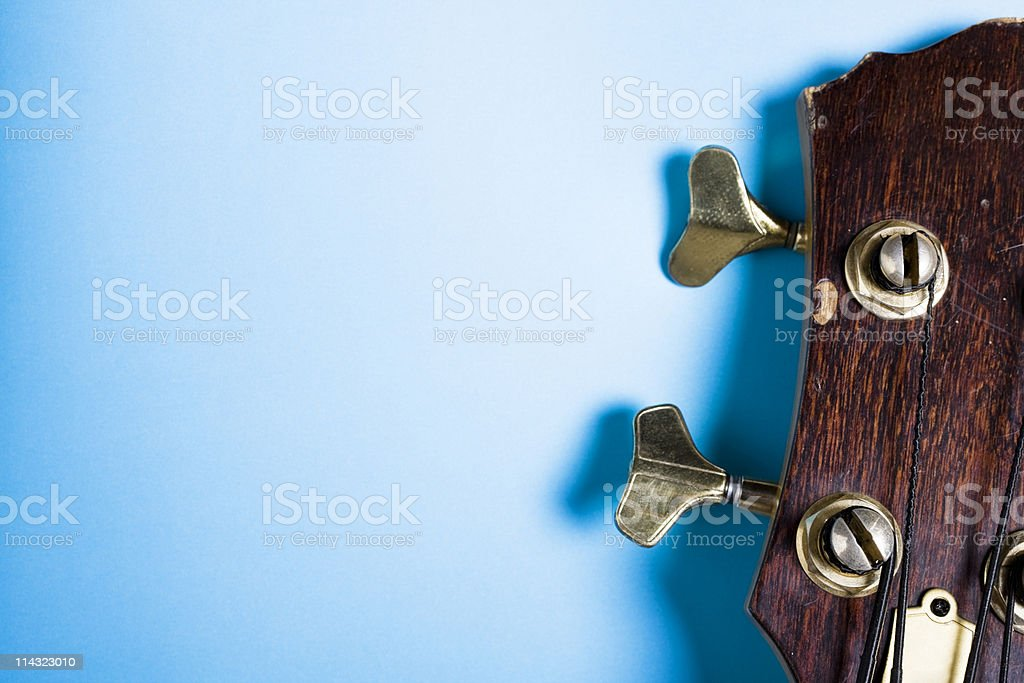 Bass guitar headstock on blue stock photo