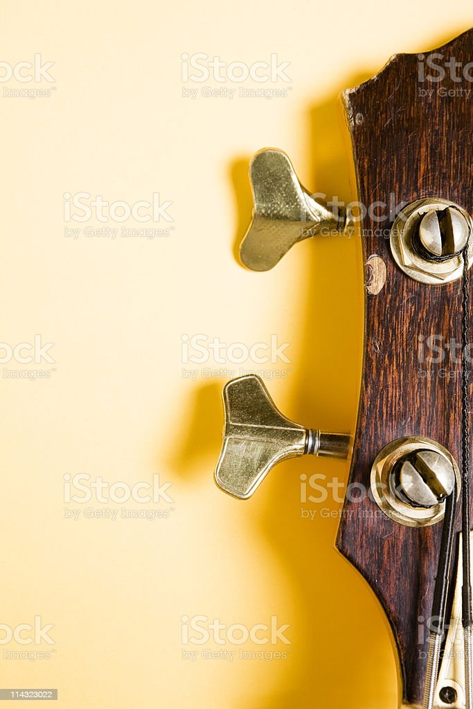 Bass guitar headstock on yellow stock photo