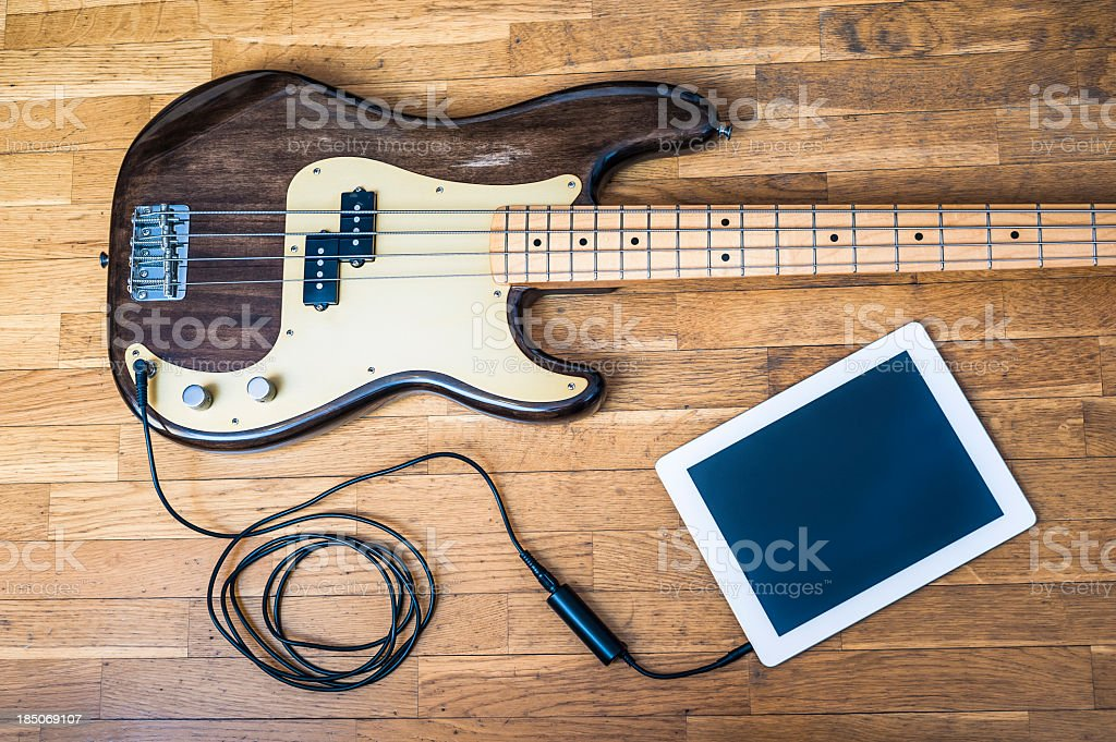Bass guitar on wooden table attached to digital tablet stock photo
