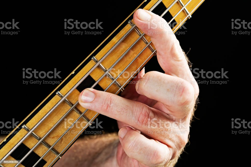 Bass guitar tutorial: Hand playing interval of an octave stock photo