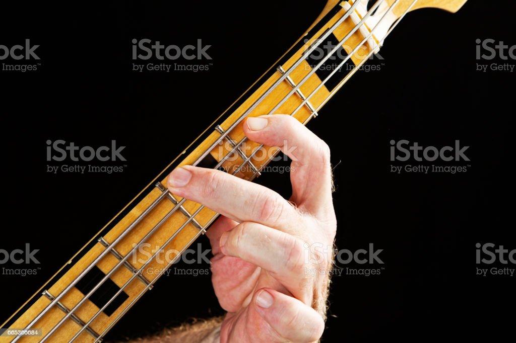 Bass Guitar tutorial: hand playing major third on electric bass stock photo