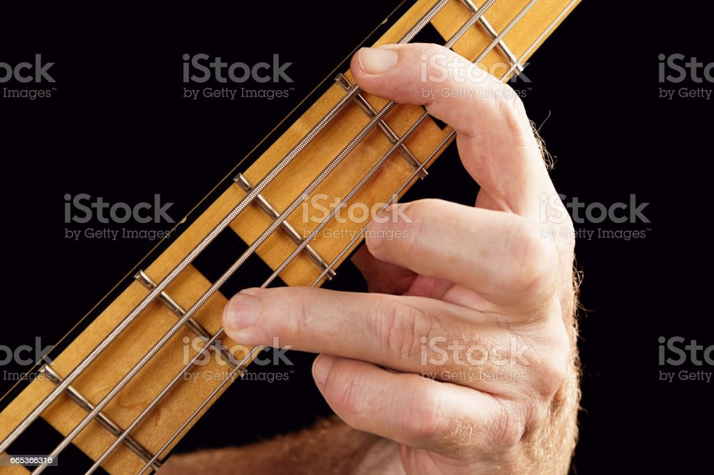 Bass guitar tutorial: hand showing interval of an octave stock photo