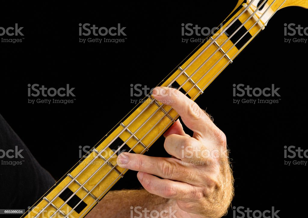 Bass guitar tutorial: hand stretching to play octave interval stock photo