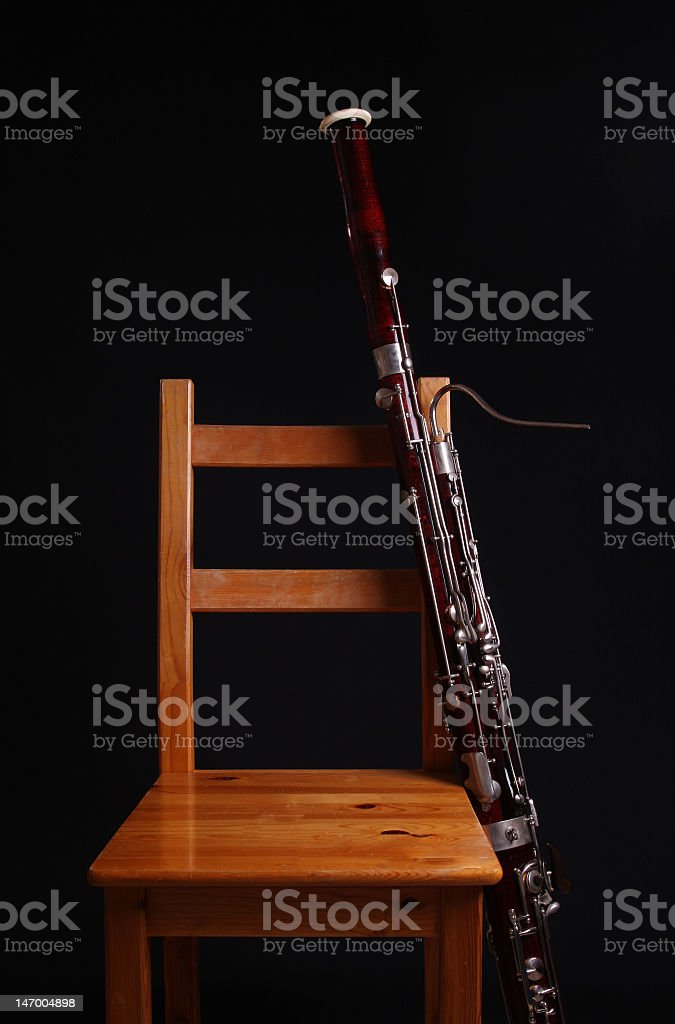 Bassoon resting on wooden chair isolated on black background stock photo