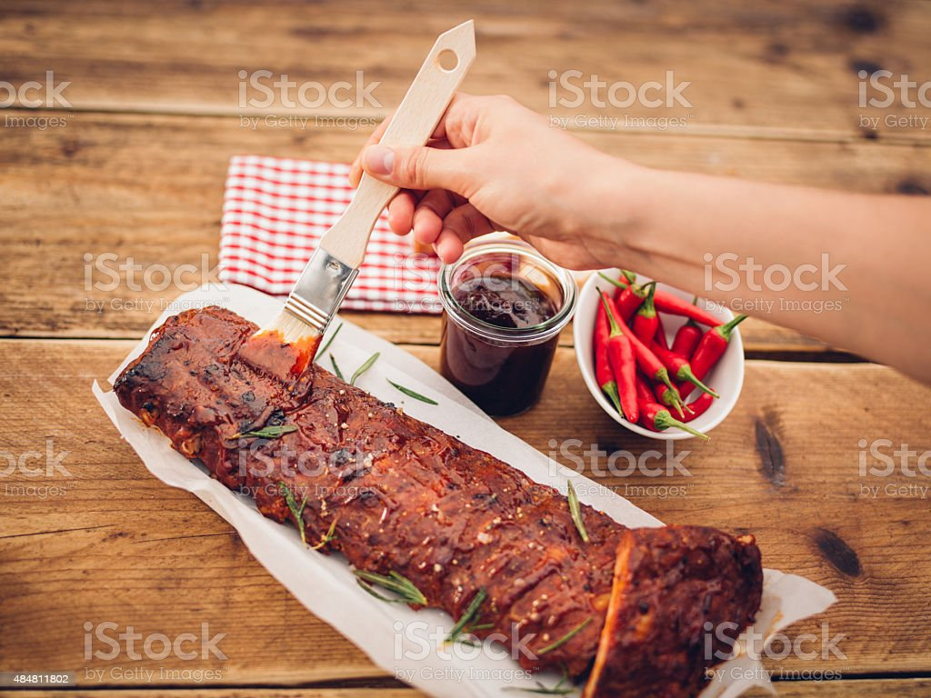 Basting being painted onto a tasty looking rack of ribs stock photo