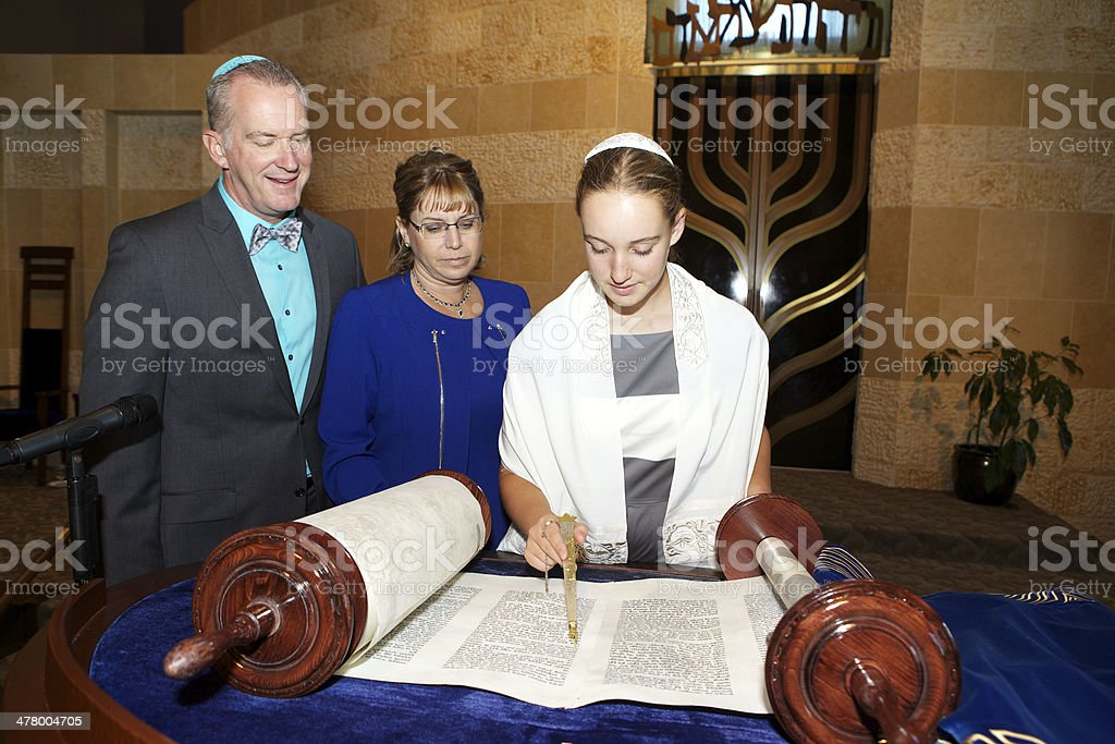 Bat Mitzvah Girl Reading the Torah with Her Parents stock photo