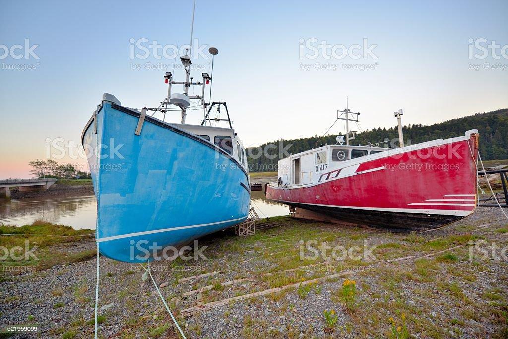 2 bateaux de pêche bleu et rouge en cale sèche stock photo