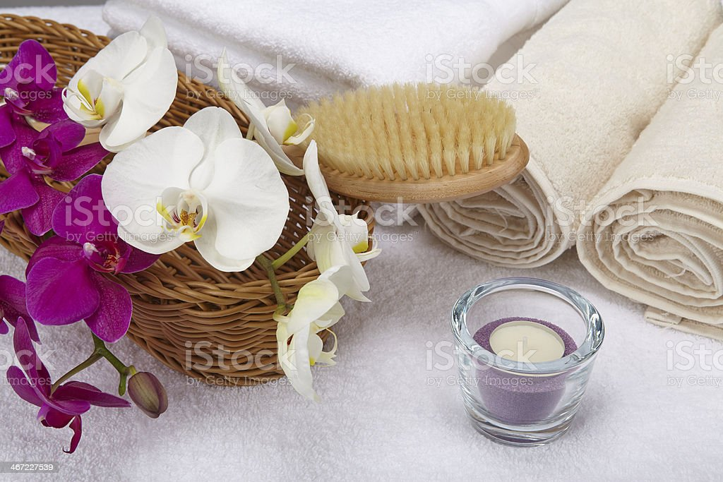 Bath brush, rolled towels, tealight and orchids stock photo