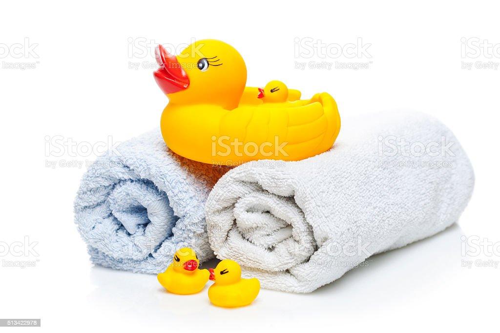 Bath towel and Yellow rubber ducks stock photo