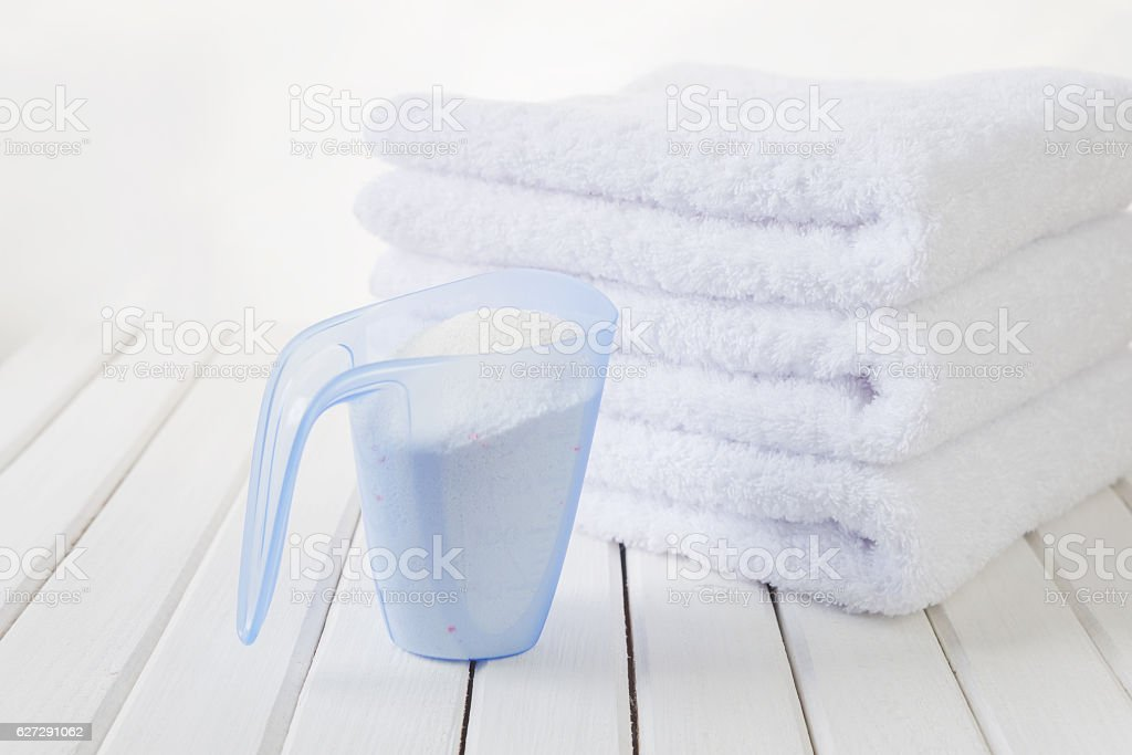Bath towels and washing powder in measuring cup stock photo