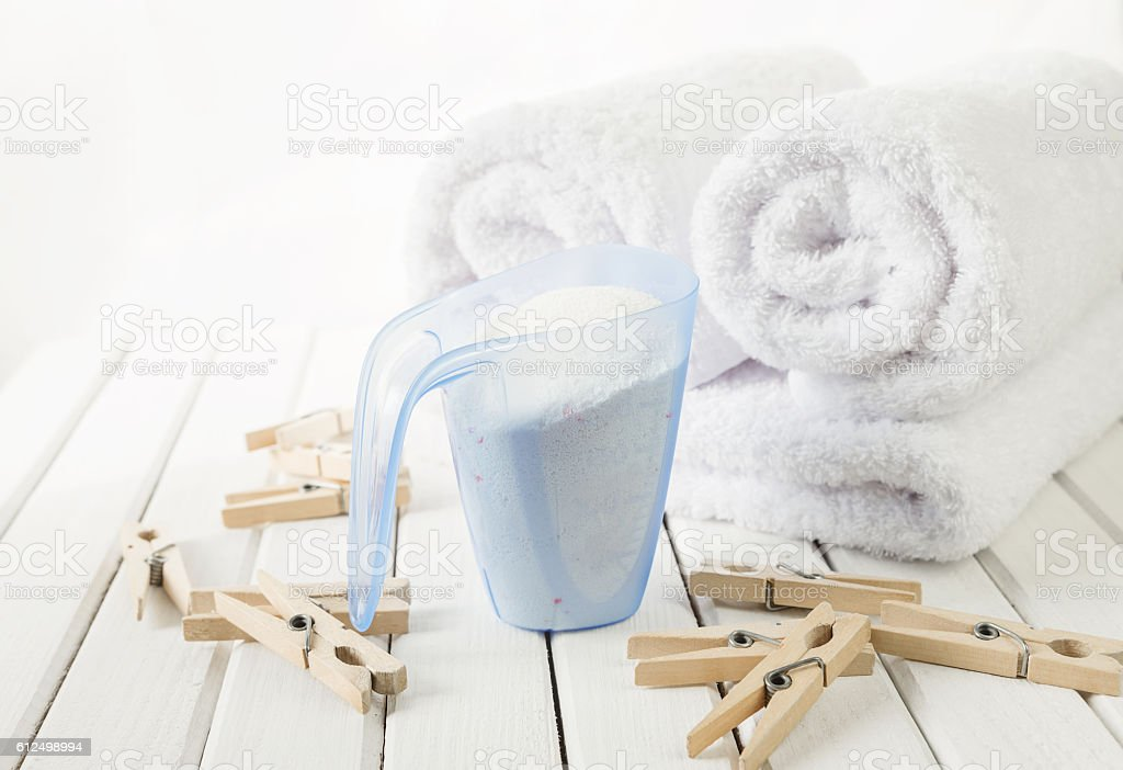 Bath towels, washing powder in measuring cup and wooden clothespins stock photo