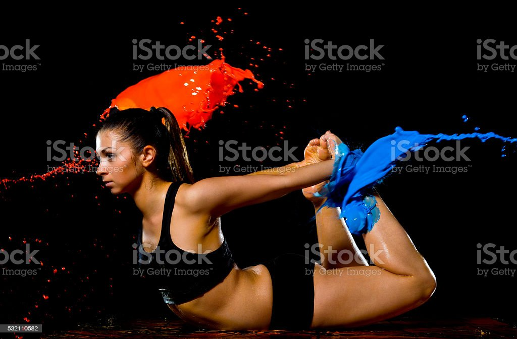 Bathed in blue paint girl doing stretching exercises stock photo